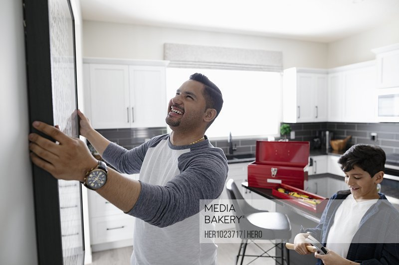 Father and son hanging picture frame in kitchen