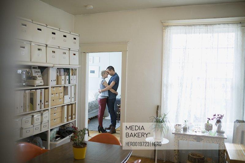 Affectionate couple hugging in apartment doorway
