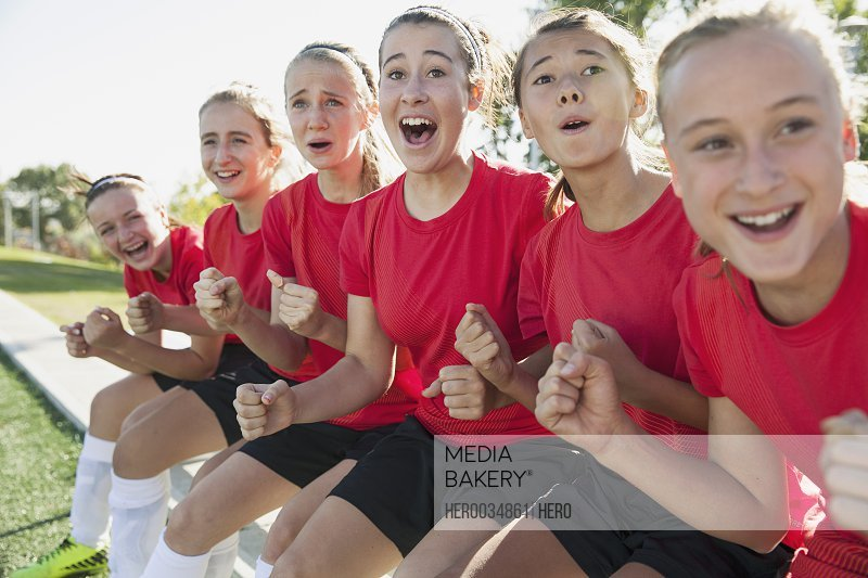 Young soccer girls cheering from the sidelines.