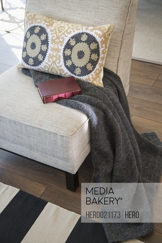 Pillow blanket and book on chair