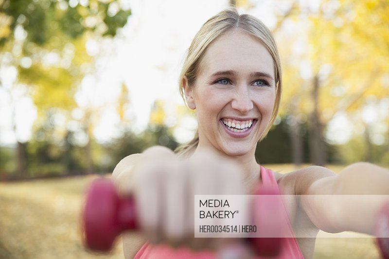 Woman using weights for outdoor workout.