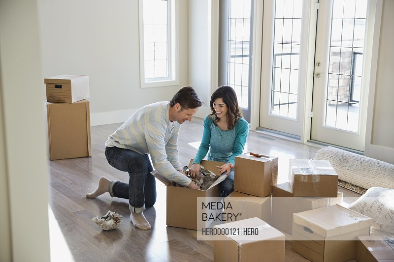 Couple unpacking cardboard boxes in new home