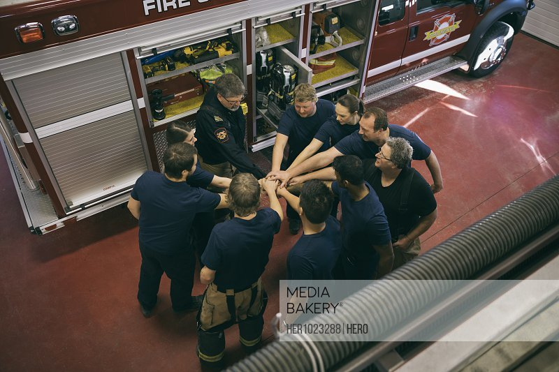 Firefighters meeting, joining hands in huddle at fire station