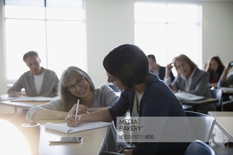 Professor helping adult education student at desk