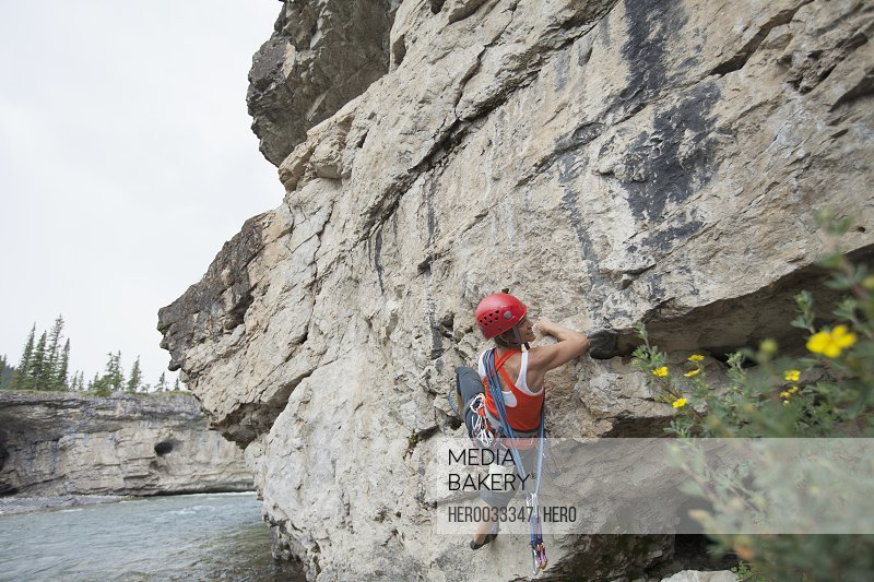 female rock climber scaling rock face