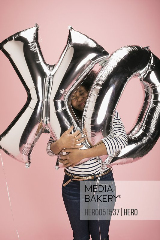 Young woman hugging silver XO balloons against pink background