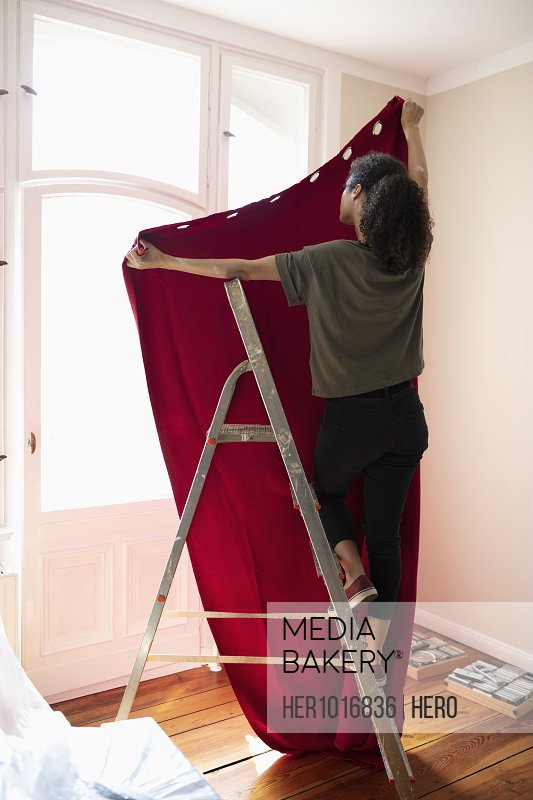 Woman on ladder hanging red curtain