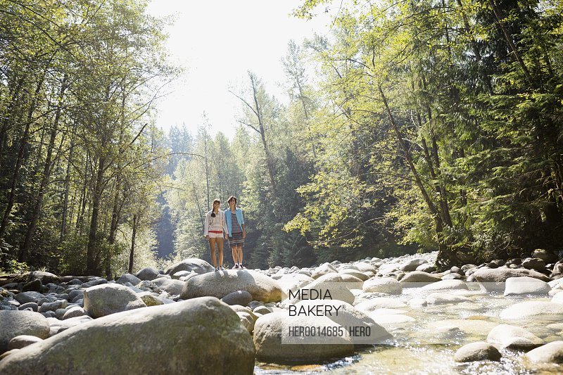 Couple standing on rock at creekside in woods