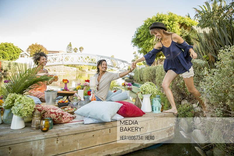 Friends enjoying picnic on raft with pillows, candles and flowers on lake