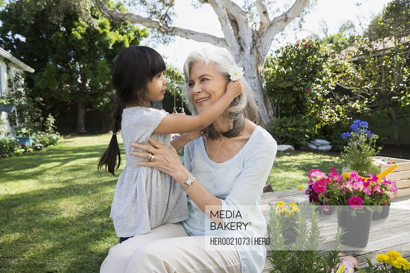 Affectionate granddaughter placing flower in grandmother hair