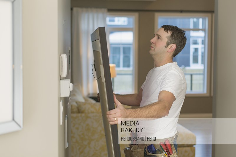 Profile of man hanging picture at home