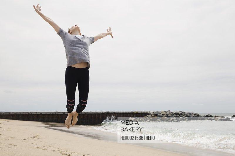 Exuberant woman jumping for joy on beach