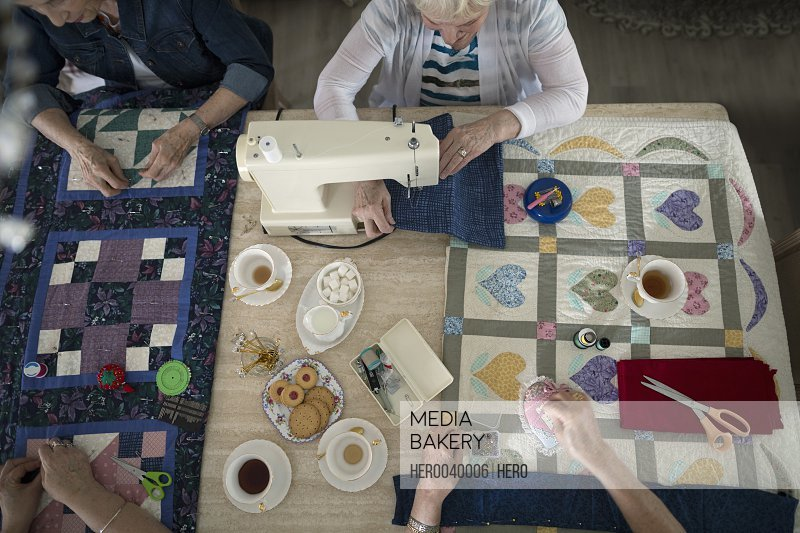 Senior women drinking tea and quilting at table