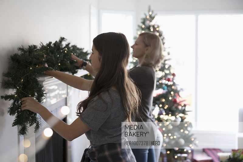 Mother And Daughter Decorating Hanging Garland On Fireplace Mantle In Living Room