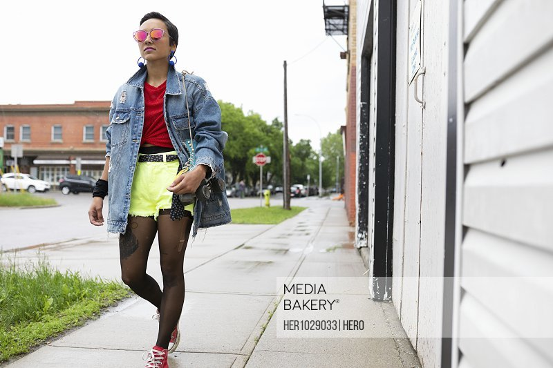Cool young woman walking on wet sidewalk, carrying roller skates