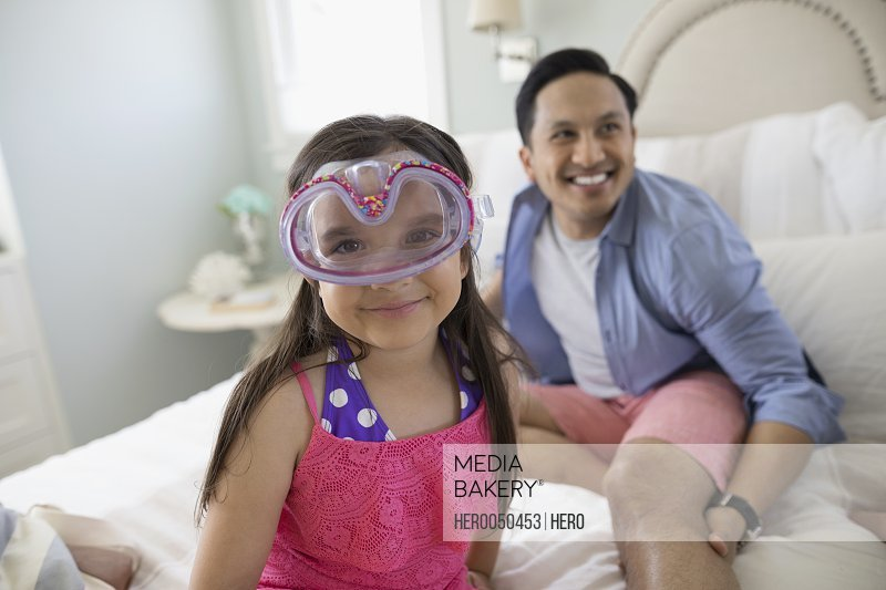 Portrait smiling girl wearing goggles upside-down on bed