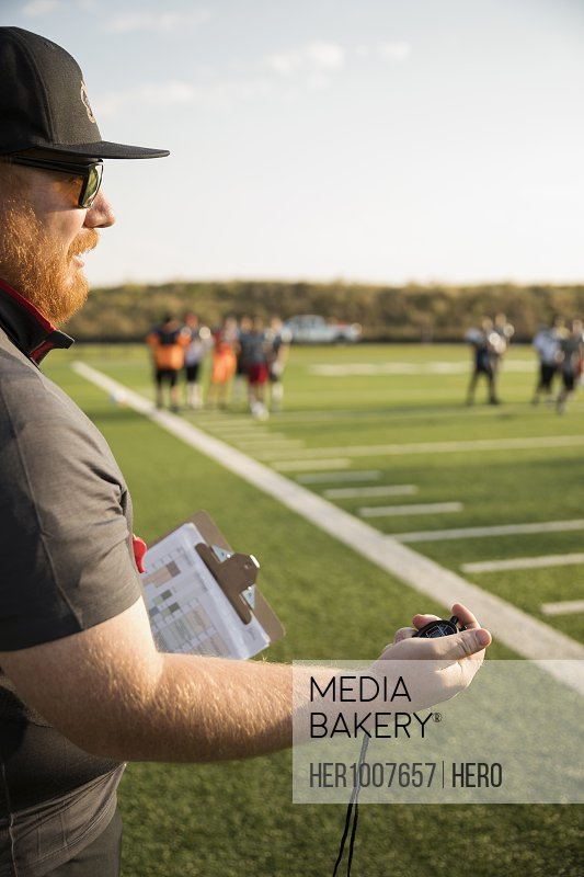 High school football coach with stopwatch timing practice on football field
