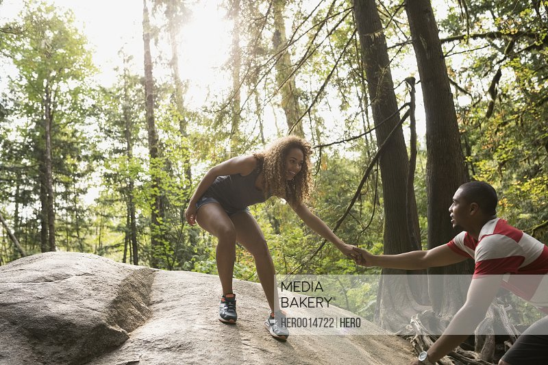 Couple holding hands on large rock in woods