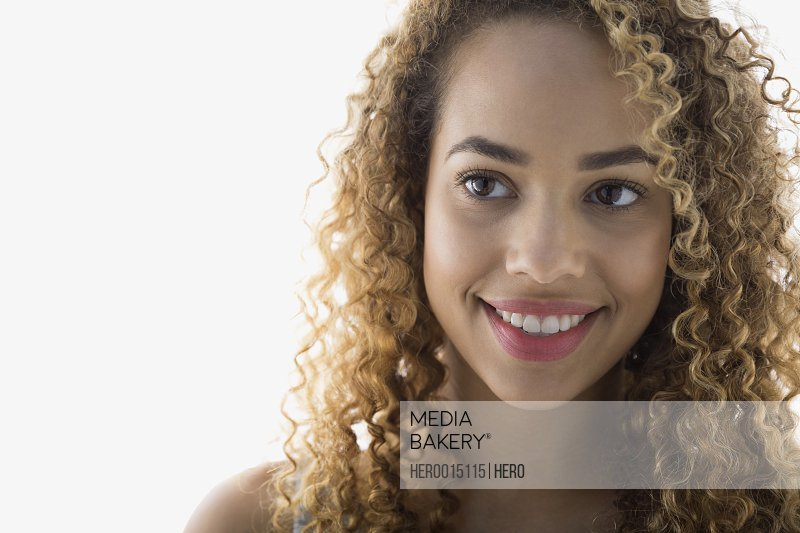 Smiling woman with curly hair looking away