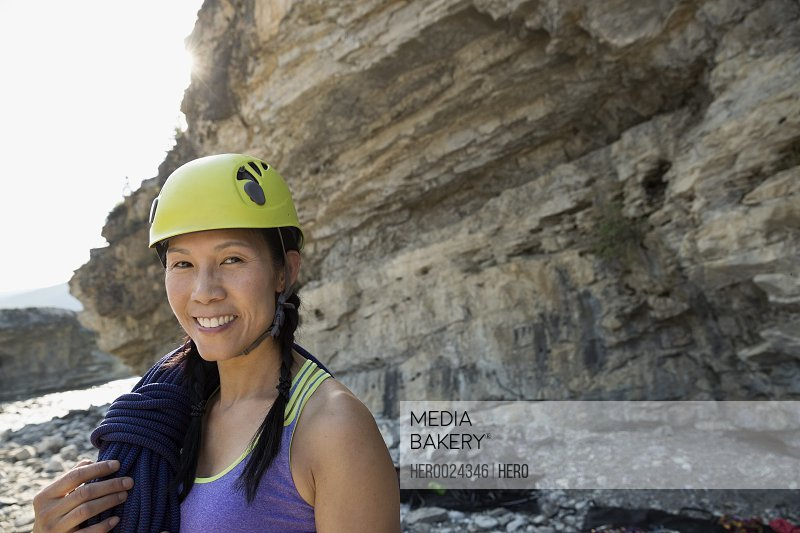 Portrait smiling female rock climber in helmet