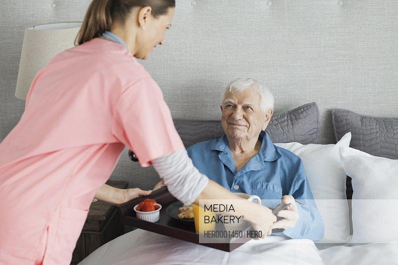 Home care nurse serving breakfast to senior man