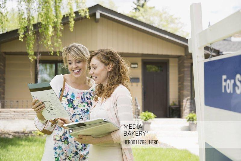 Realtor showing woman paperwork outside house