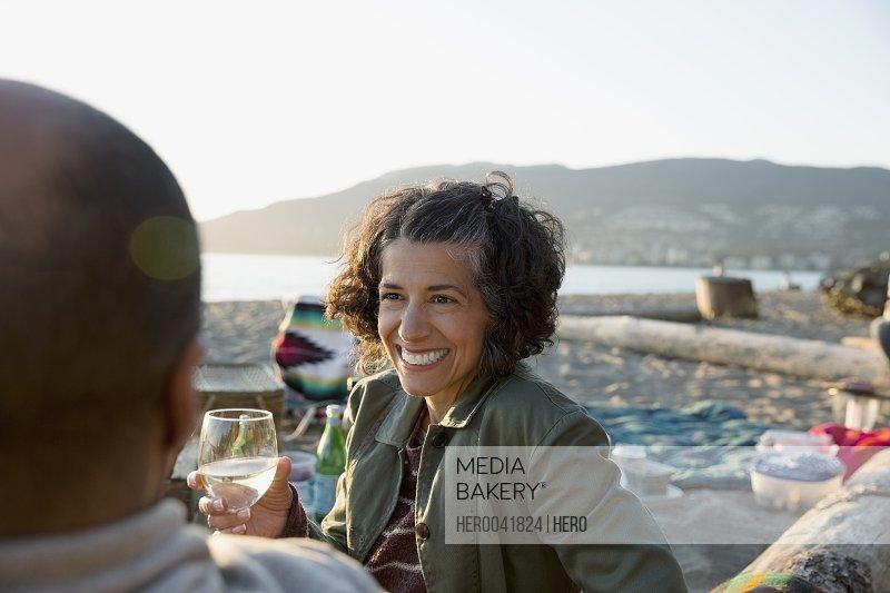 Smiling couple drinking wine enjoying picnic on beach