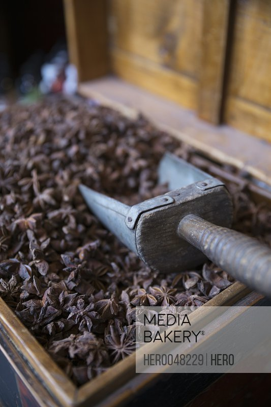 Close up star anise and scoop in wooden box in spice shop