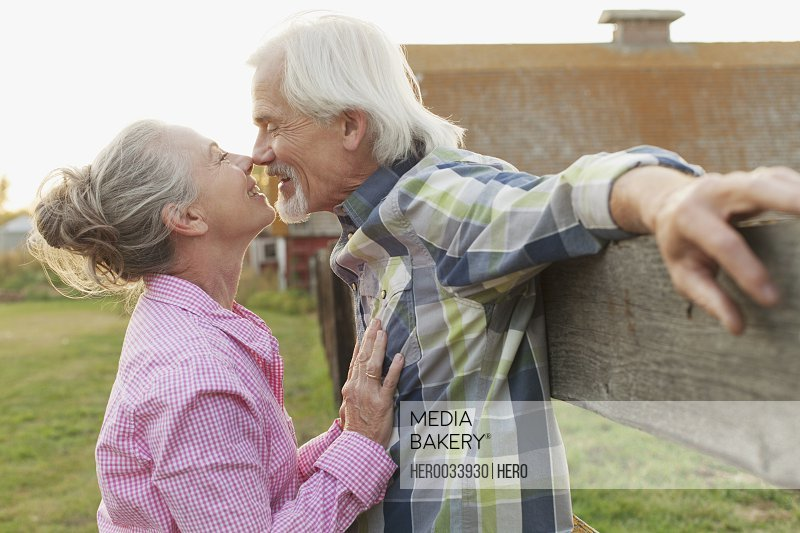 Mature couple being affectionate outdoors.