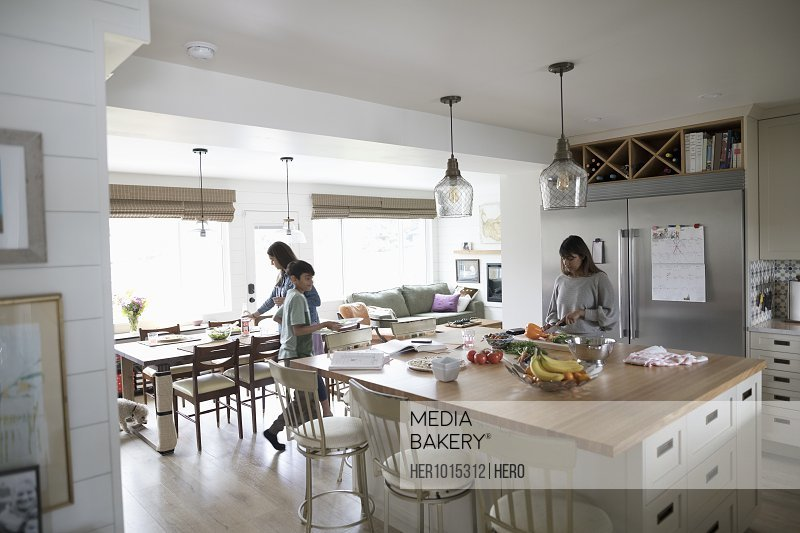 Mother cooking with tween daughter and son set the table in kitchen
