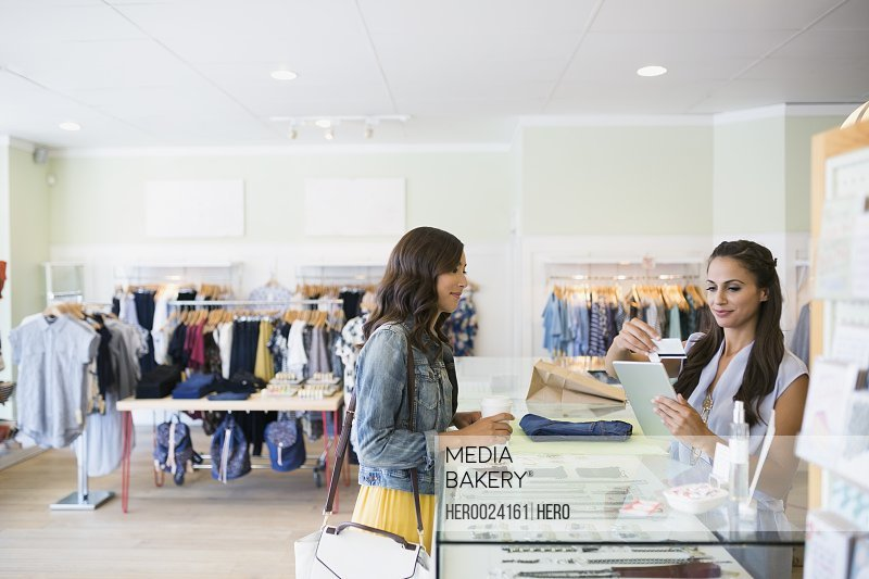 Worker swiping credit card reader digital tablet shop