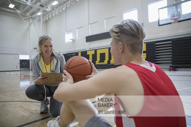Female coach coaching male basketball player in college gymnasium