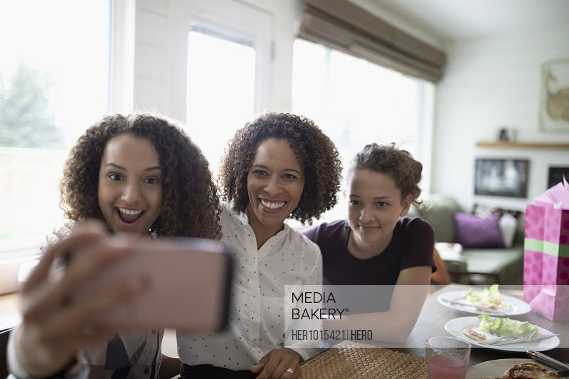 Happy mother and daughters taking selfie with camera phone