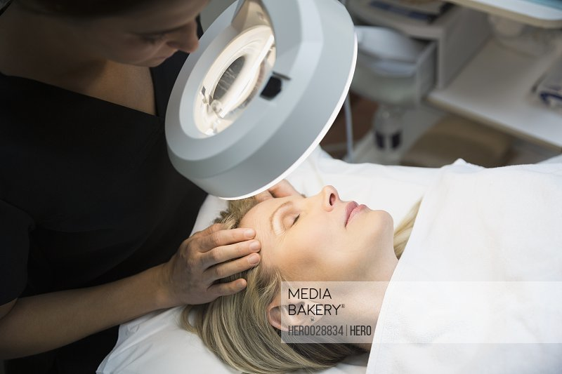 Aesthetic technician examining womans face under light