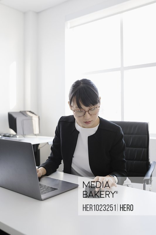Businesswoman at laptop using smart phone in office