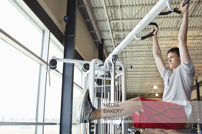 Man doing hanging leg raises in fitness center