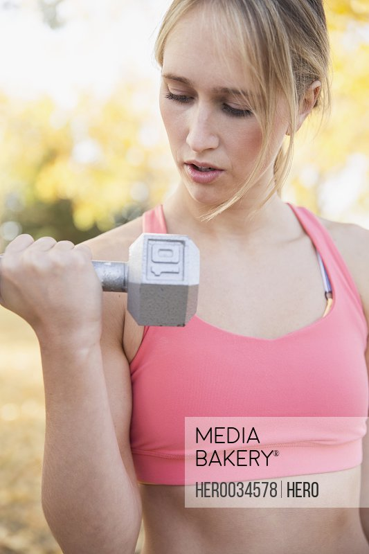 Young woman using weights during outdoor workout.