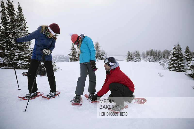 Family preparing, putting on snowshoes in snow