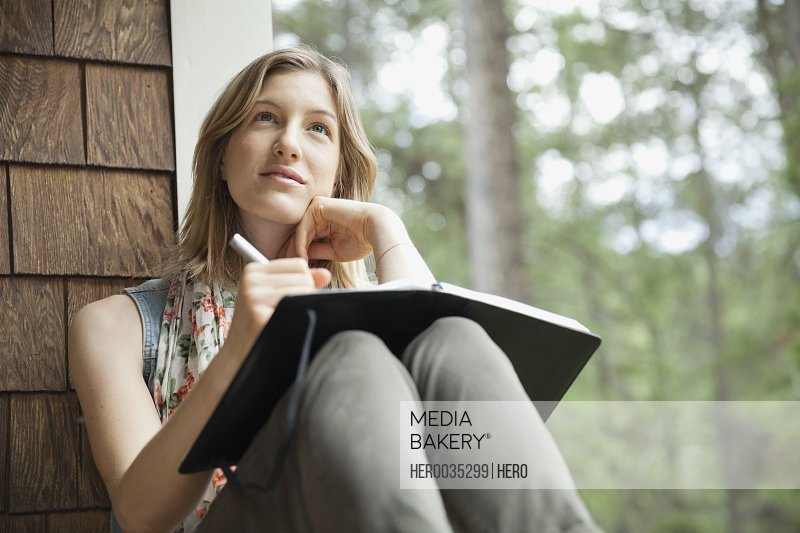 Thoughtful young woman sitting on cabin porch with journal