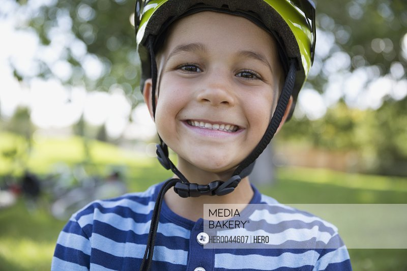 Close up portrait boy wearing bike helmet at park
