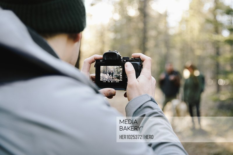 Man with digital camera photographing friends hiking in woods