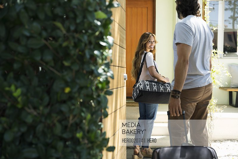 Couple with luggage arriving at vacation house