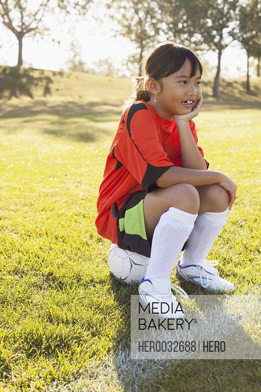 girl soccer player sitting on soccer ball on sidelines