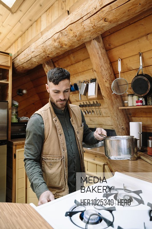 Man cooking at stove in cabin