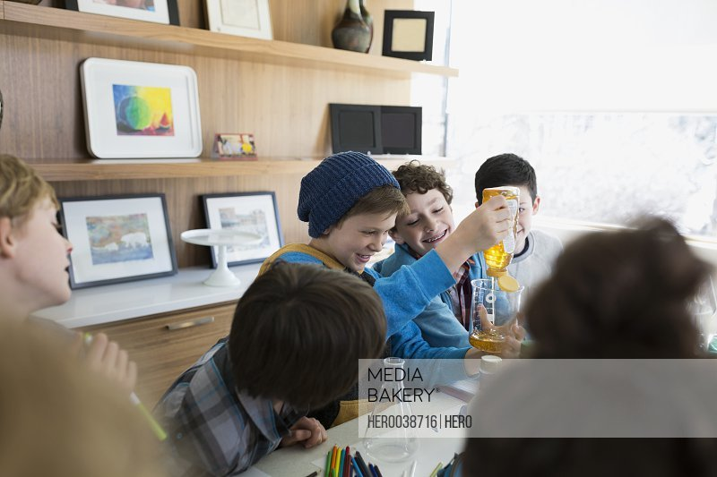 Boys conducting science experiment at dining table