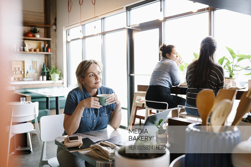Thoughtful woman working and drinking coffee in cafe