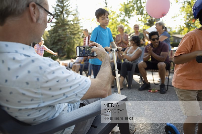 Man with camera phone videoing kids parade at summer neighborhood block party