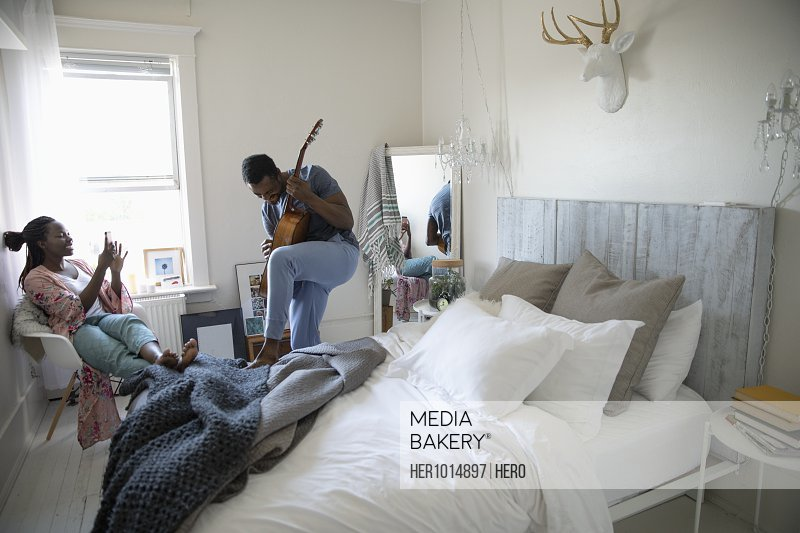 Young woman with camera phone photographing boyfriend playing guitar in bedroom