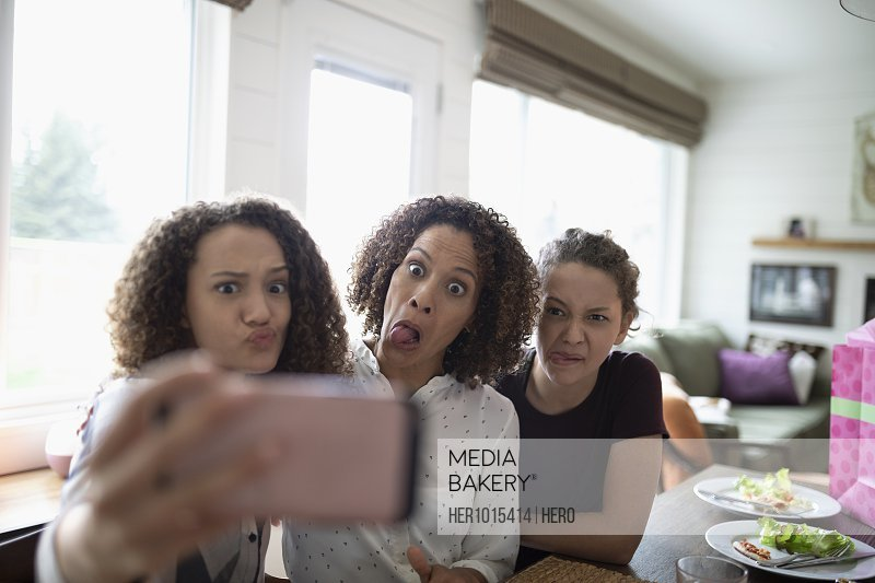 Playful mother and daughters making faces, taking selfie with camera phone