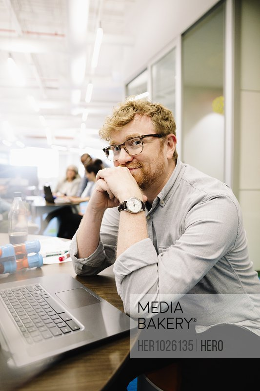 Portrait confident creative businessman working at laptop in office